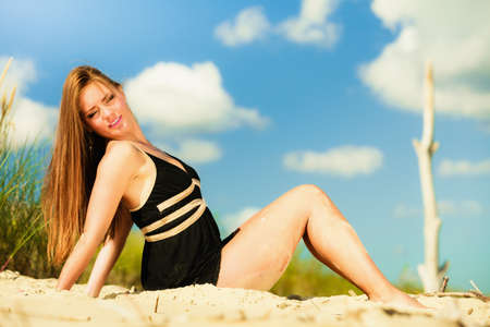 freetime: Summer vacation day freetime concept. Sitting woman body sunbathing delight on beach seaside. Stock Photo