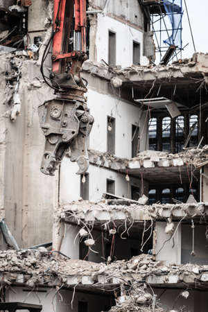 dismantling: Urban scene. Dismantling of a house. Building demolition and crashing by machinery for new construction. Industry. Stock Photo