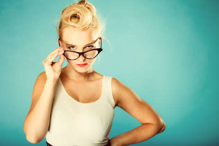 oculist: Optometrista, oculista y el concepto oftalmólogo. Joven rubia retro pin up mujer enojada con gafas en el estudio. Retro y fotos de época.