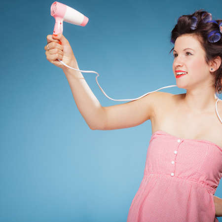 drier: Young woman preparing to party having fun, funny girl styling hair with hairdreyer retro style on blue