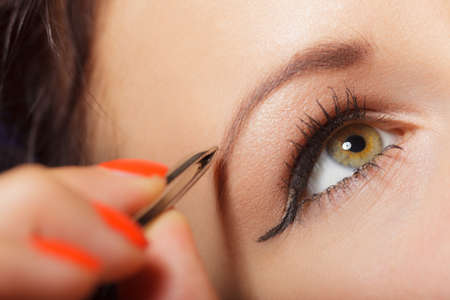pinzas: Parte del primer de la cara, mujer depilarse las cejas depilaci�n con pinzas. Chica depilarse las cejas.