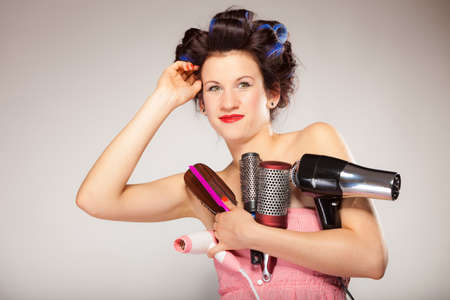 women hair: Young woman preparing for date having fun, cute girl with curlers styling hair with many accessories comb brush hairdreyer on  gray
