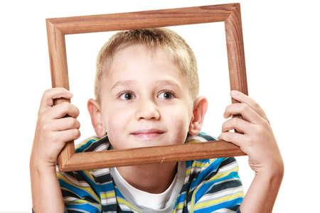 framing: Portrait of little smiling blonde boy child holding photo frame framing his face studio shot isolated on white Stock Photo