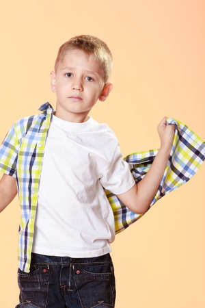 7 year old boys: little serious blonde boy child trying on shirt orange background