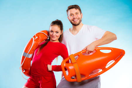 Accident prevention and water rescue. Young man and woman lifeguard couple on duty holding buoy lifesaver equipment on blue photo