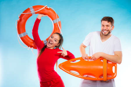 Accident prevention and water rescue. Young man and woman lifeguard couple on duty holding buoy lifesaver equipment having fun on blue photo