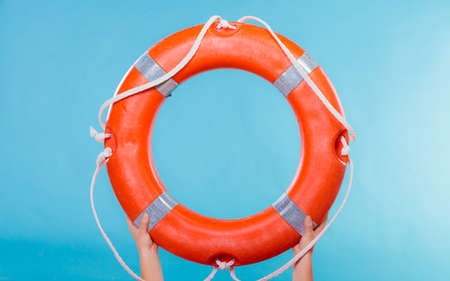 lifebelt: Accident prevention and water rescue. Life buoy ring lifebelt in female hands studio shot blue background