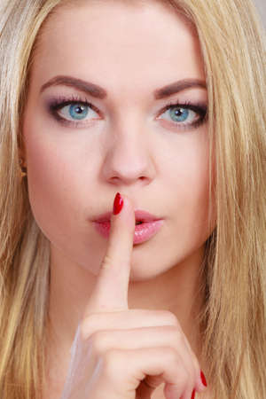 secrecy: Closeup woman asking for silence or secrecy with finger on lips hush hand gesture. On gray background Stock Photo