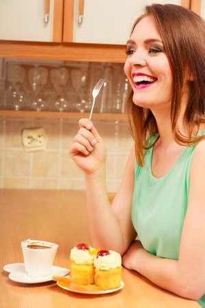 gula: Mujer con la taza de caf� gourmet comer deliciosa crema de torta dulce de la magdalena y naranja. Glot�n chica sentada en la cocina con la bebida caliente que tiene el desayuno. El apetito y el concepto de la gula. Foto de archivo