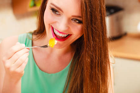 gluttony: Happy woman eating delicious gourmet sweet cream cake cupcake with fruits. Glutton girl having breakfast in kitchen. Appetite and gluttony concept. Stock Photo