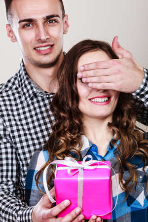 gifting: Couple and holiday concept. Smiling young man surprising cheerful woman with gift box covering her eyes with hand Stock Photo