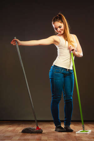 mops: Cleanup housework concept. Funny cleaning lady young woman mopping floor, holding two mops new and old dark background