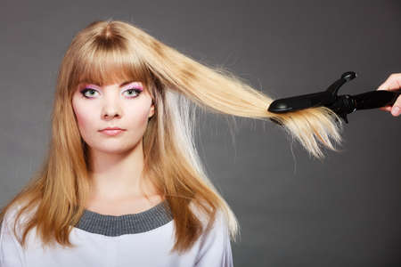Hairstyling. Attractive blonde woman long haired making hairstyle hairdo with electric hair iron straightener gray background photo