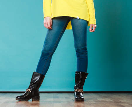 Fashion. Woman legs in denim trousers black boots casual style on blue photo