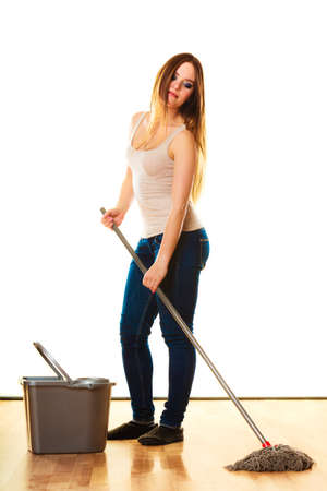Spring cleaning concept. young woman mopping floor, standing with old mop and bucket white background photo