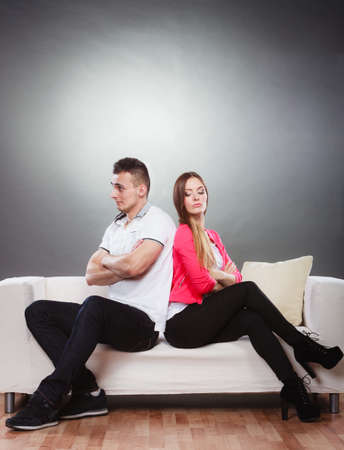 impasse: Bad relationship concept. Man and woman in disagreement. Young couple after quarrel sitting on sofa back to back Stock Photo