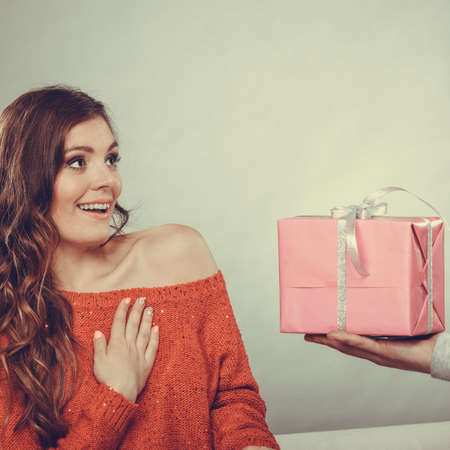 taking a wife: Couple and holiday concept. man holding present in hands surprising cheerful woman with gift box