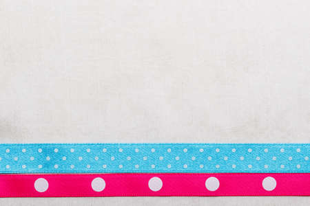 pink satin: Festive celebration party frame. Polka dot blue and pink satin ribbon on white cloth background