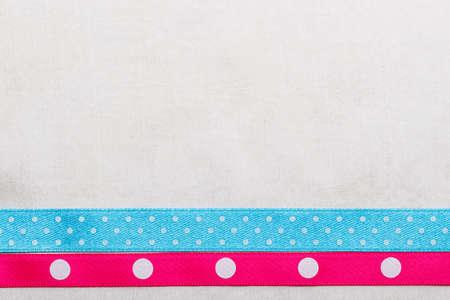 bordered: Festive celebration party frame. Polka dot blue and pink satin ribbon on white cloth background
