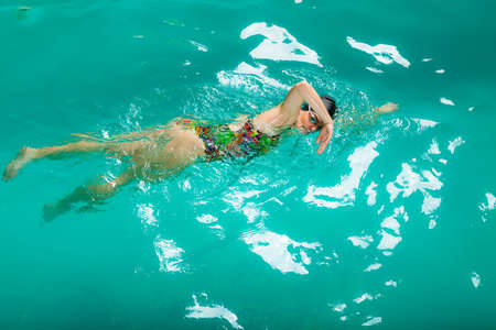 copysapce: Swimming. Competition and recreation. Woman swimmer breathing performing crawl style. Poolside.