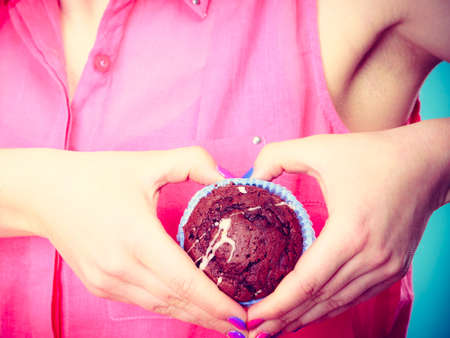 indulging: Sweet food sugar make us happy. woman holds chocolate muffin in hand making heart shape with fingers around cake closeup