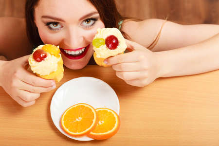 sneaking: Delighted woman hiding behind table sneaking and eating delicious cake with sweet cream and fruits on top. Appetite and gluttony concept. Stock Photo