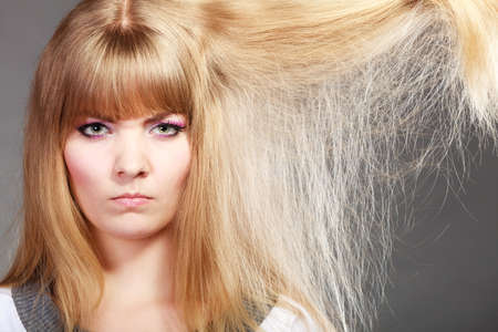 damaged: Haircare. Blonde woman with her damaged dry hair angry face expression gray background