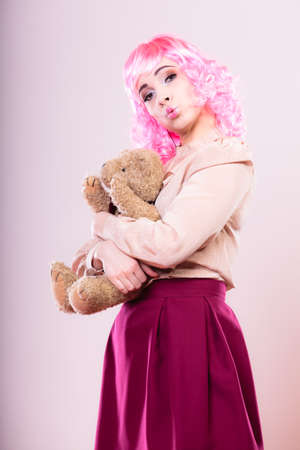 childlike: Mental disorder concept. Young childlike woman wearing like puppet doll holding teddy bear toy studio shot
