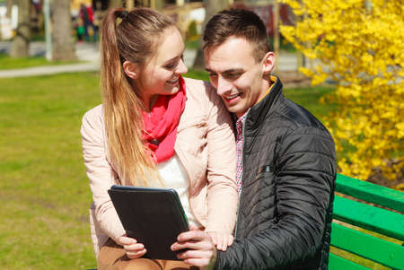 websurfing: Modern technologies leisure and relationships concept. Young couple with pc computer tablet sitting on bench outdoor websurfing on internet Stock Photo