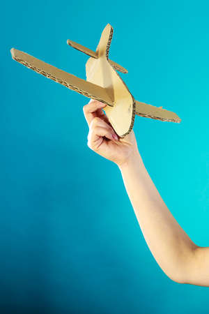 holding paper: Flight travel or aerophobia concept. Female hand holding paper airplane blue background
