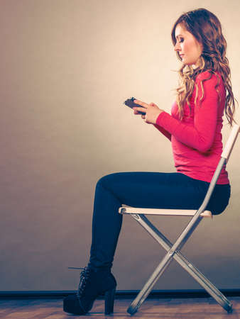 absorbed: Woman using mobile phone sitting in chair. Absorbed girl texting messages. New technology.