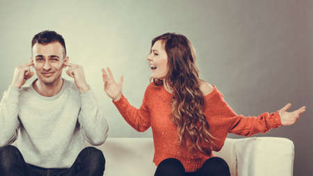 relationship love: couple having argument - conflict, bad relationships. Angry fury woman screaming man closing his ears.