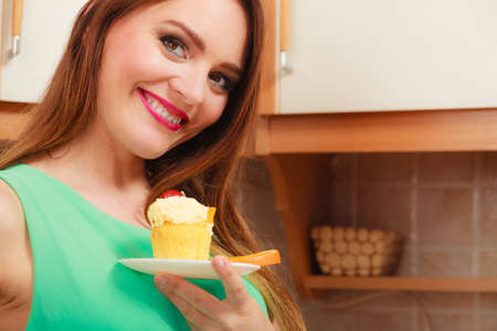 gula: Mujer que sostiene el delicioso pastel con crema de dulce y frutos en la parte superior. El apetito y el concepto de la gula.