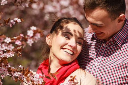 Dating. Young woman and man walking, couple in love relaxing in blossoming cherry trees park at sunny spring day photo