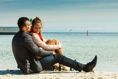 loving couple spending leisure time together at beach hugging side view photo