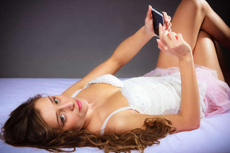 woman dialing phone number: Texting and calling concept. Beauty young long haired woman lying on bad holding smartphone and showing something. Stock Photo