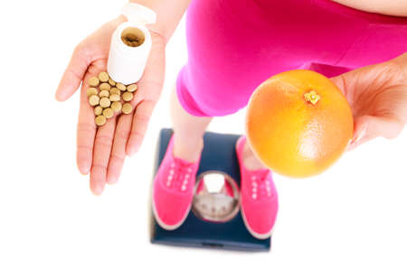 natural health: Young woman girl standing on weighing scale holding pills and grapefruit. Choice between synthetic vitamins natural. Health care. Healthy lifestyle nutrition concept. Isolated on white background.