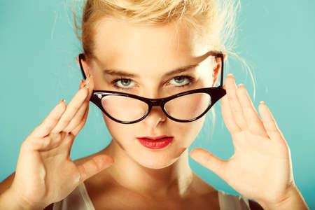 oculist: Optometrista, oculista y el concepto oftalmólogo. Mujer rubia joven con gafas en el estudio. Fotos retro, vintage.