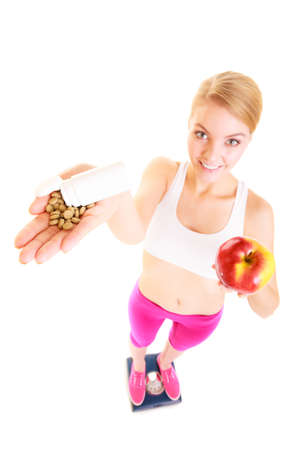 natural health: Young woman girl standing on weighing scale holding pills and apple. Choice between synthetic vitamins natural. Health care. Healthy lifestyle nutrition concept. Isolated on white background.