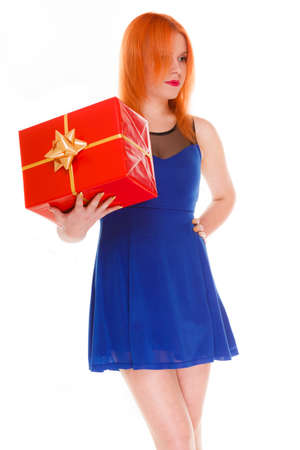 red head girl: People celebrating holidays, love and happiness concept - red head girl in blue dress looked pensively holds red gift box studio shot isolated. Time gifts Stock Photo