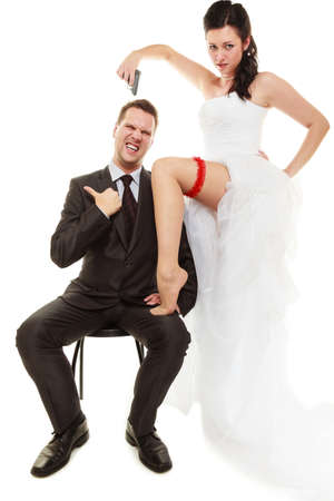 emancipation: Wedding day. Betrayal and emancipation concept. Bride with gun in white dress and groom in suit isolated on white. Stock Photo