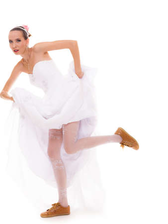 Wedding day. Running bride funny young woman wearing sport shoes isolated on white background photo