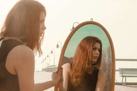 mirror?: Concepto de la soledad Soledad. Mujer joven pensativa que mira el reflejo en el espejo al aire libre en la puesta del sol