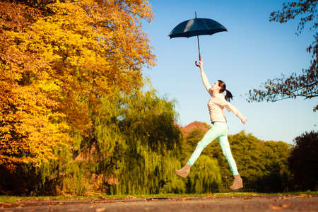 Happiness freedom and people concept. Casual young woman teen girl jumping with blue umbrella in autumnal park, having fun outdoor photo