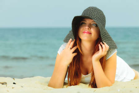 Holidays, vacation travel and freedom concept. Beautiful redhaired happy girl in hat on beach. Stock Photo