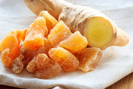 crystallized: Closeup dried candied crystallized ginger pieces and fresh rhizome root on rustic table. Healthy eating, home remedy for nausea, colds. Stock Photo