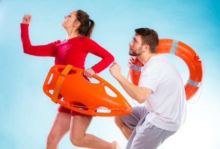 life belt: Accident prevention and water rescue. man and woman lifeguard couple on duty running with with life belt lifesaver equipment on blue