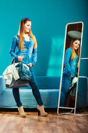mirror: Fashion and shopping. Woman in full length wearing denim with bag. Attractive female shopper looking in mirror, standing in clothes store. Blue color