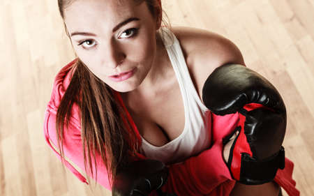 feminist: Emancipation and feminist. Defense concept. Young fit woman boxing. Indoor. Stock Photo