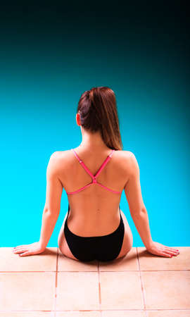 active lifestyle: Sport active lifestyle. Sporty woman female swimmer muscular fit body  in swimsuit relaxing at poolside indoor swimming pool. Stock Photo